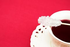 Swizzle sugar stick. Victorian white cup with red herbal tea and sugar swizzle stick. Focus on the stick Royalty Free Stock Images