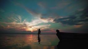 swobodny ruch M??czyzny bieg wzd?u? wody kobieta z dzieckiem na jeziorze przy zmierzchem Sylwetki dzieci troszk? zbiory