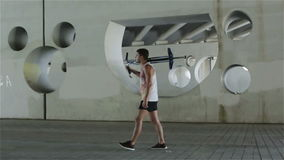 swobodny ruch Młoda atleta niesie kij z wiosną na ramieniu przechodzi obok na chodniczku zbiory