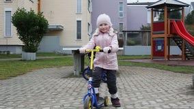 swobodny ruch Małej dziewczynki jechać kopnięcie hulajnoga w jardzie zdjęcie wideo