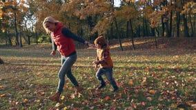 swobodny ruch Szczęśliwa matka i syn bawić się w jesień parku z żółtymi liśćmi zdjęcie wideo