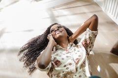 Swoman de sourire pensant à l'avenir tout en parlant à un téléphone Femme de couleur se trouvant sur le plancher Photos libres de droits