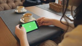 Swoman usando el teléfono celular móvil con la pantalla táctil verde en café almacen de video