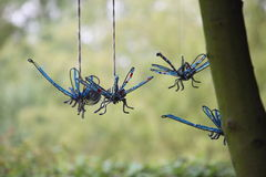 Swooping dragonfly wind chime on green background Stock Photography