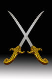 Sword. Identical swords with golden handle in black background Stock Photography