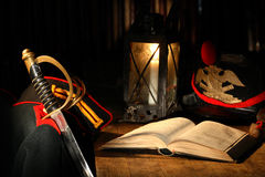 Sword And Book. Vintage still life with ancient sword and military uniform near table with book Stock Photos