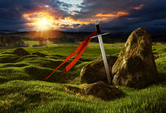 Sword in the dramatic sunny landscape. Sword on the meadow with stones under the dramatic sky. Storm heaven and sun lights. Photos montage with 3D render royalty free illustration