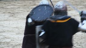 Sword fight between two men wearing historic armor suits and steel helmets. Stock footage stock footage
