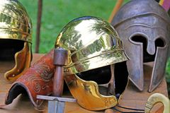 Sword and helmets of ancient Roman origin and medieval helmets o. Roman helmets and medieval helmets of brave knights and soldiers Stock Photos