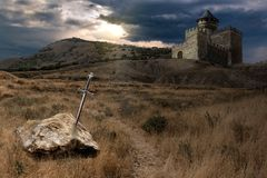 Sword of King Arthur. Legend of King Arthur and his escalibur sword thrown into stone, against the backdrop of a knight s castle, collage stock photo
