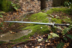 The sword lies on the mossy stone. Two-handed sword is lying on the moss-covered stone Royalty Free Stock Photography