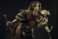 Sword and rose. Brutal barbarian warrior with sword smelling the rose over dark background Royalty Free Stock Photos