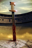 Sword in the sand. A gladiator's sword soaked with blood, nailed in the sand of the Roman coliseum Royalty Free Stock Images
