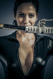 Sword, girl military woman posing with guns. Royalty Free Stock Images