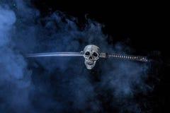 Sword Through Skeleton Skull. Foggy scene of a katana sword stuck through a skeleton skull Stock Image