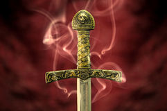 Sword in smoke. Medieval sword shrouded in smoke fantasy background royalty free stock photography