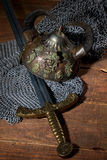 Sword and the soldier's helmet with horns on a wooden background Stock Image