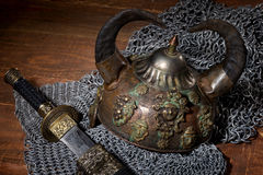 Sword and the soldier's helmet with horns on a wooden background Royalty Free Stock Images