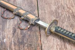 Sword steel blade samurai and scabbard easel ancient on old wooden surface floor with copy space.  Royalty Free Stock Photo