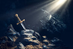 Sword in the stone excalibur. High contrast image of Excalibur, sword in the stone with light rays and dust specs in a dark cave Royalty Free Stock Photo
