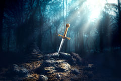 Sword in the stone excalibur. High contrast image of Excalibur, sword in the stone with light rays and dust specs in a dark forest Stock Photos