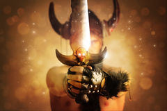 Sword of warrior. Fantastical portrait of a warrior with focus on powerful sword with skull against magical background of rays of light Royalty Free Stock Photos