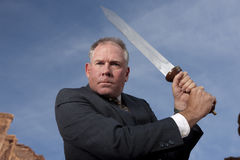 Sword Wielding Businessman. Businessman gives an intense look as he holds a sword, ready for battle. Horizontal shot Royalty Free Stock Photos
