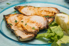 A swordfish dishes pics, among lemons cut, on a glass dish, over Royalty Free Stock Images