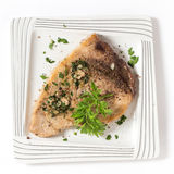 Swordfish steak from above. Cooked peppered swordfish steak with a parsley and garlic butter sauce on a plate viewed from above royalty free stock image