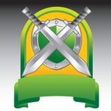 Swords and shield in green display. Green display with crossed swords and a shield Stock Image