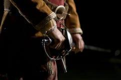 Swordsman do mosqueteiro o sobre um fundo preto Imagens de Stock Royalty Free