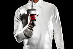Swordsman holding fencing sword. Close-up of swordsman holding fencing sword on black background Stock Photography