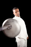 Swordsman practicing with fencing sword. Portrait of swordsman practicing with fencing sword on black background Royalty Free Stock Images