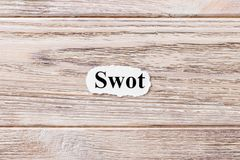SWOT. Strengths Weaknesses Opportunities Threats of the word on paper. concept. Words of SWOT on a wooden background.  Stock Photography
