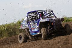 SXS blue buggy on the berm. ARNCOTT, UK - MAY 4: An unnamed driver competing in the UK SXS RZR series hits a right hand turn at speed causing mud to fly into the Stock Photos