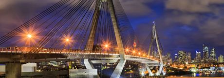 Sy Anzac bridge Close CBD Pan. Dark sunset panorama of Sydney city CBD skyline from Harbour with steel cables and columns of Anzac bridge in Inner West with royalty free stock photography