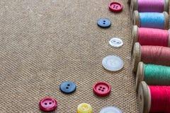Sy bearbetar många den olika färgrika tråden, många olika knappar på träbakgrund Arkivbilder