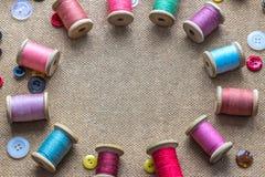 Sy bearbetar många den olika färgrika tråden, olika knappar på träbakgrund Arkivbild