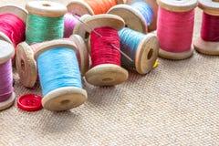 Sy bearbetar många den olika färgrika tråden, visaren, knappar på träbakgrund Royaltyfri Fotografi
