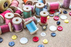 Sy bearbetar många den olika färgrika tråden, visaren, många olika knappar på träbakgrund Royaltyfri Foto