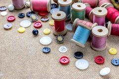 Sy bearbetar många den olika färgrika tråden, visaren, många olika knappar på träbakgrund Royaltyfri Bild