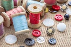 Sy bearbetar många den olika färgrika tråden, visaren, många olika knappar på träbakgrund Fotografering för Bildbyråer