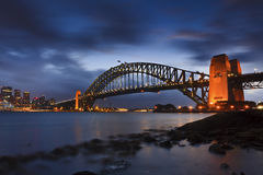 Sy Bridge Set Low Tide. AUstralia Sydney harbour bridge side view at sunset illuminated lights under blurred cloudy sky during low tide time of sydney harbour Royalty Free Stock Photos
