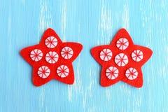 Sy den röda julstjärnaprydnaden Sy de vita filtcirklarna till de röda filtstjärnorna genom att använda den röda tråden moment Top Royaltyfria Bilder
