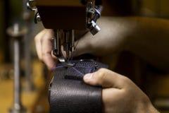 Sy en askhäftklammer på svart läder royaltyfria foton