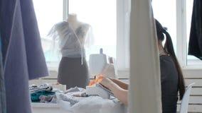 Sy för hobby och ett små och medelstora företagbegrepp Den unga nätta kvinnasömmerskan syr på symaskinen Skräddare som gör ett pl arkivfilmer