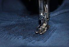Sy, häftklammer ett hål i mörk jeans eller att sticka sweatpants med en symaskin Del av symaskin- och grov bomullstvillcloseupen royaltyfri foto