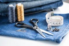 Sy hjälpmedel med jeanstyg royaltyfri foto