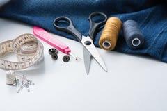 Sy hjälpmedel- och jeanstyg på den vita tabellen royaltyfri foto