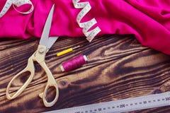 Sy hjälpmedel, rosa tyg och tråden på en träbakgrund Fotografering för Bildbyråer